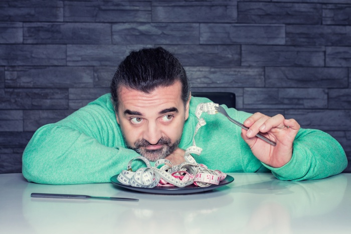 Man on diet, looking unhappy, plate filled with measuring tape instead of food, diet and eating disorder concept